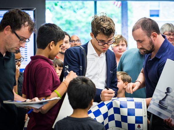 El campeón mundial Carlsen firmando autógrafos.